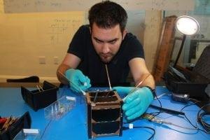 A Spire engineer building a CubeSat