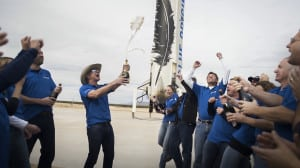 The Blue Origin team celebrates with founder Jeff Bezos at the site of the New Shepard rocket booster landing.
