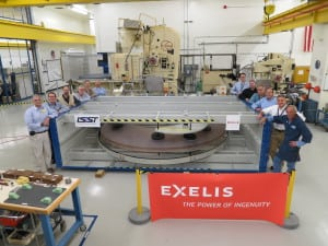 "Exelis optics employees pose with ""a big glass paperweight"" that will become the secondary mirror for the Large Synoptic Survey Telescope."
