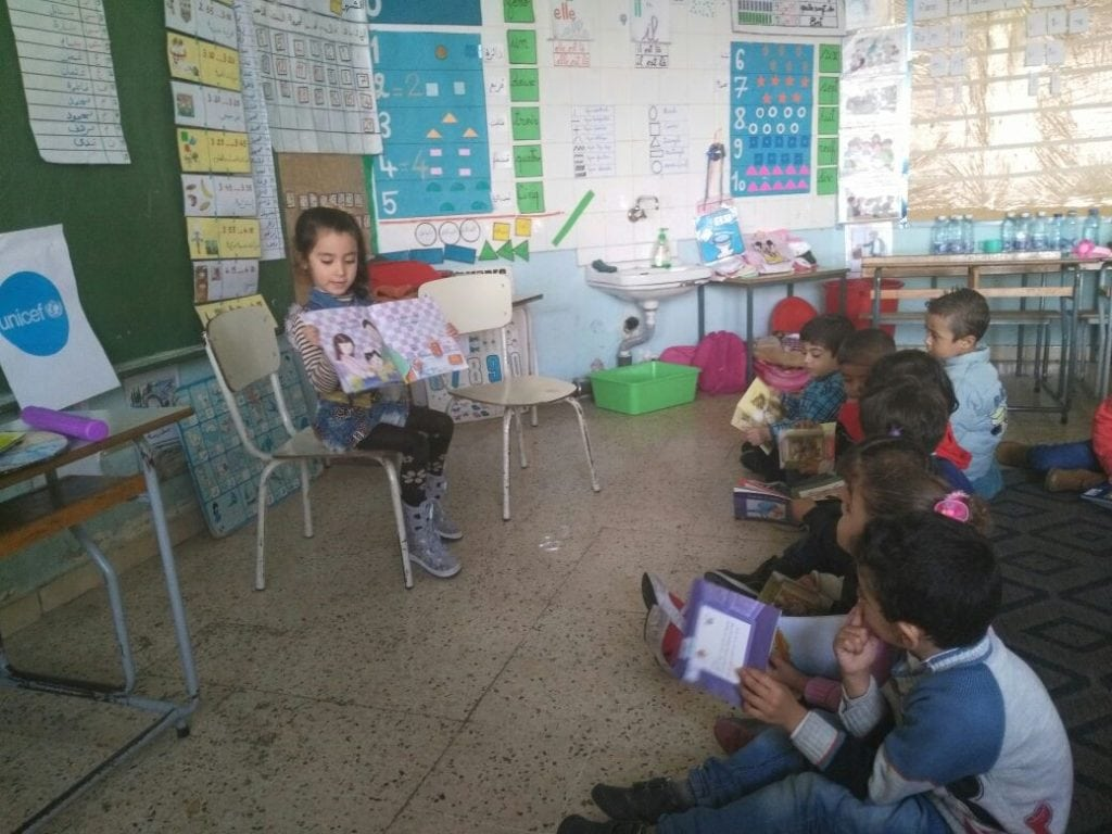 Children reading books donated by Thuraya at a school in Lebanon