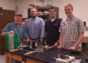 Students and teachers part of the Auburn University Small Satellite Program pose with a cubesat