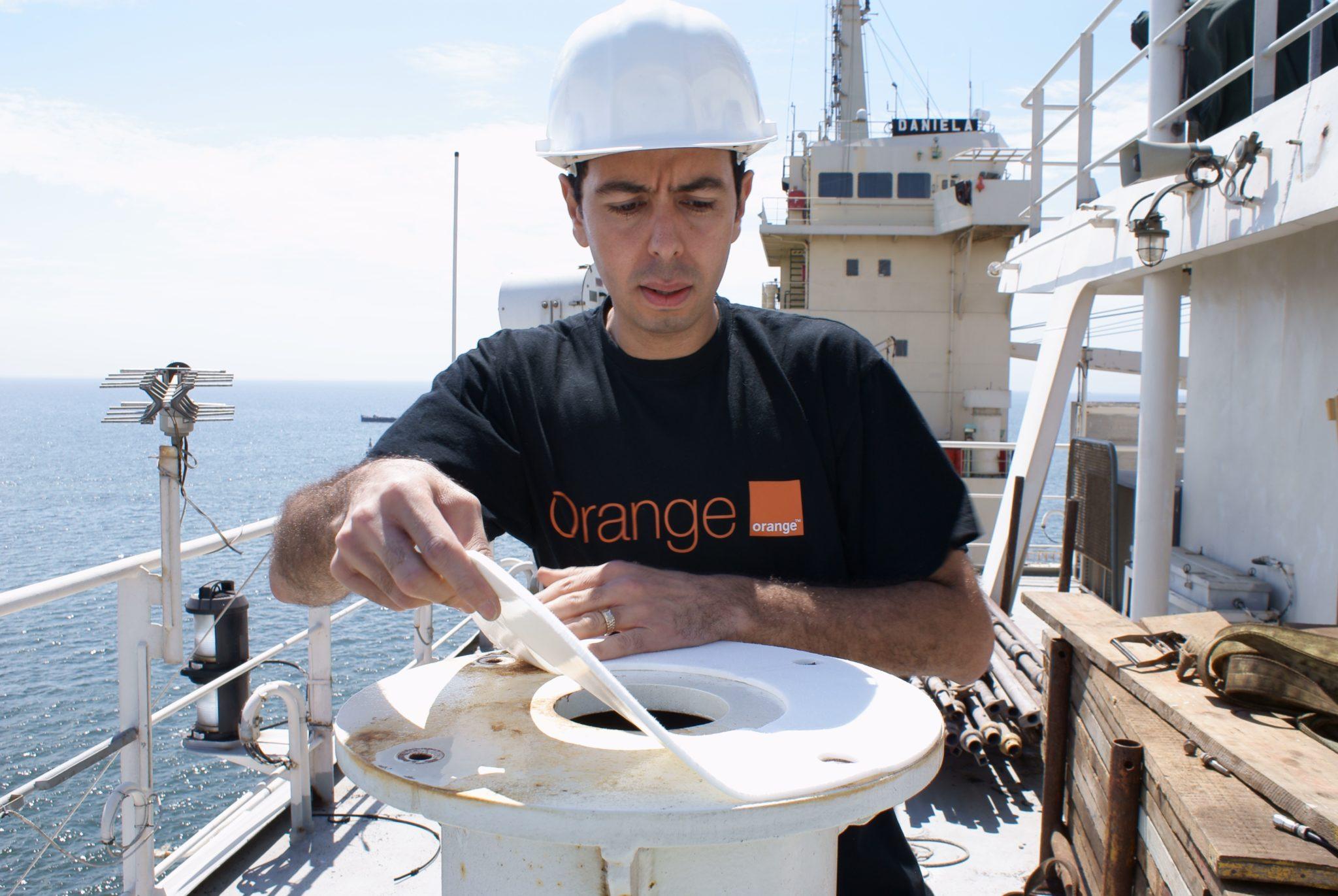 Orange engineer installs network equipment on board.