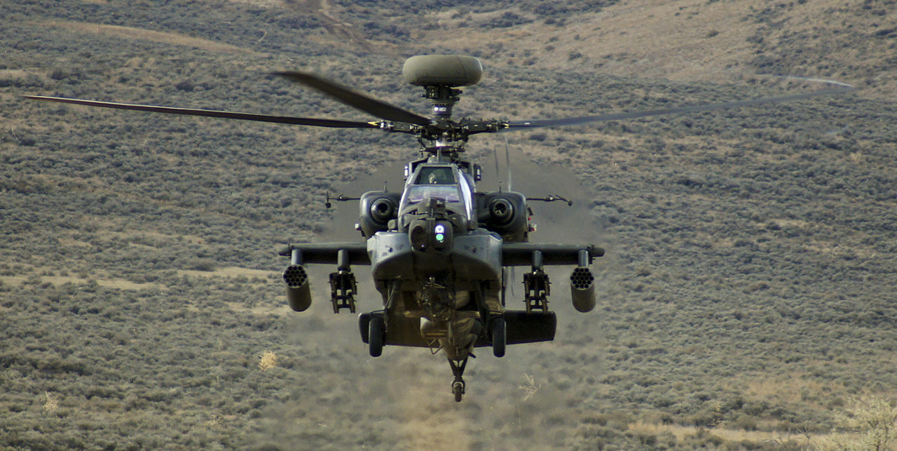 An AH-64 Apache rises from behind a hill during a training exercise at Yakima Training Center. Photo: Wikimedia.