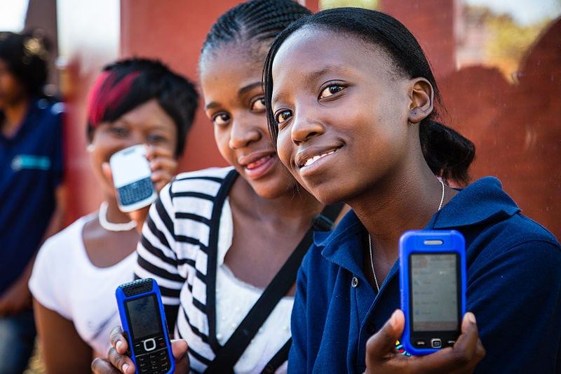 Students in Africa show off their mobile phones. Photo: Wikimedia.