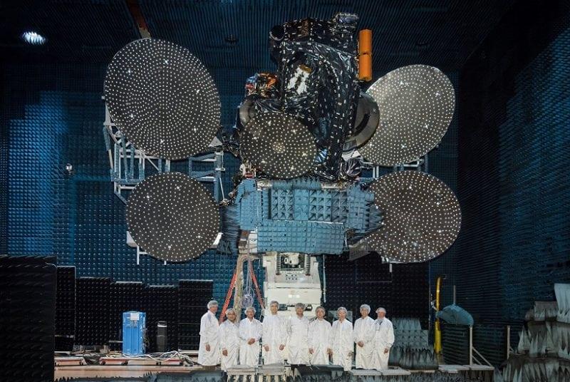 AsiaSat technicians stand in front of the AsiaSat 9 satellite. Photo: AsiaSat.