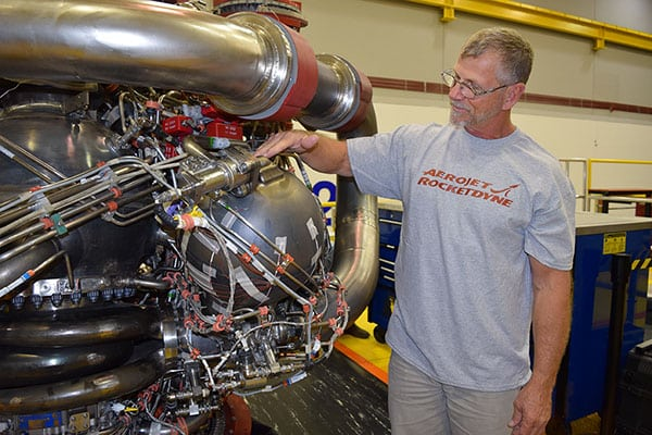An Aerojet Rocketdyne technician inspects the 3D-printed pogo accumulator assembly on an RS-25 development engine at the Aerojet Rocketdyne facility located at NASA's Stennis Space Center. Photo: Aerojet Rocketdyne.