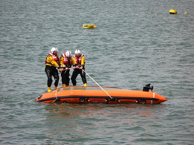 A crew of the Royal National Lifeboat Institution show their skills during a capsize drill. Photo: Wikimedia.