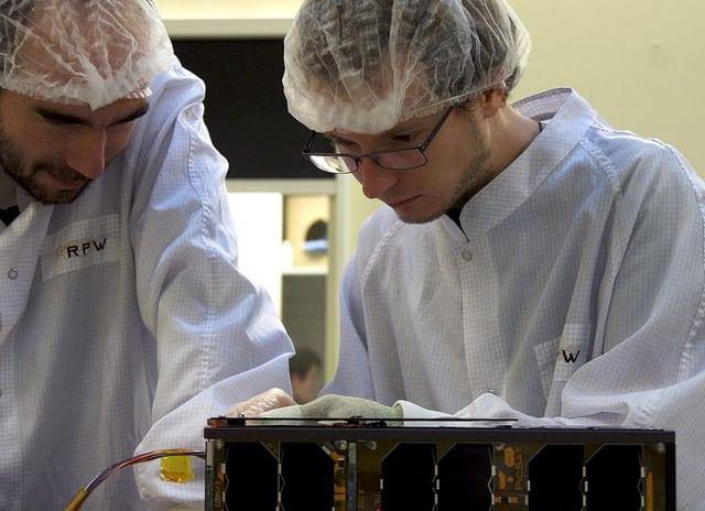 Sylvestre Lacour (left) and Lester David (right) working on PicSat integration. Credit: Observatoire de Paris.