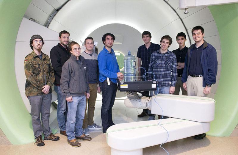 Virginia CubeSat Constellation students in the Hampton University Proton Therapy Institute Test Chamber. L-R: James Flynn (ODU), John Noon (Virginia Tech), Ben Connelly (UVA), Anthony DeFilippis (Virginia Tech), David Khanan (UVA) , Nathan Gaul (UVA), Michael Ford (UVA), William Cheng (UVA) and Patrick Bebermeyer (UVA). Photo: VSGC.