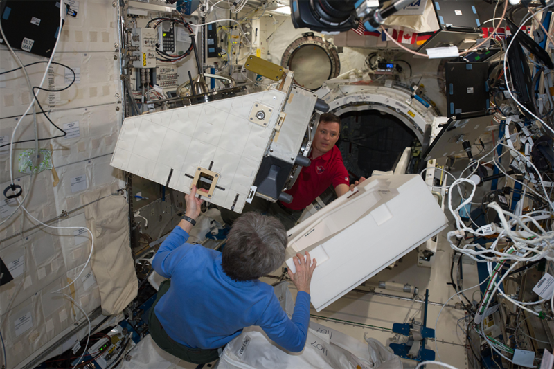 NASA astronauts Peggy Whitson and Jack Fischer move a new payload on to the NanoRacks External Platform to prepare for deployment from ISS. Photo: NASA.
