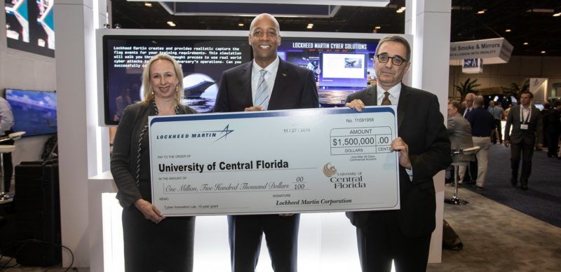 The Lockheed Martin Cyber Innovation Lab at the University of Central Florida will equip future cyber professionals. Lockheed Martin's Amy Gowder and Tom Warner and the University of Central Florida's Dr. Michael Georgiopoulos (left to right) commemorate a contribution at the Interservice/Industry Training, Simulation and Education Conference in Orlando, Florida. Photo: Lockheed Martin