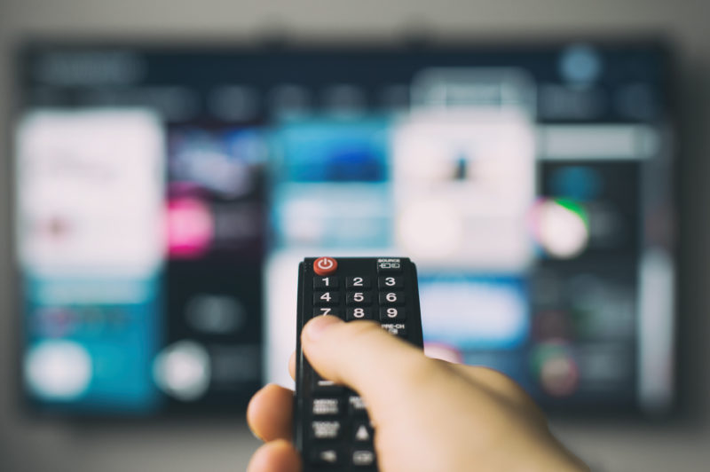 Person holding TV remote control. Photo: Sat>IP